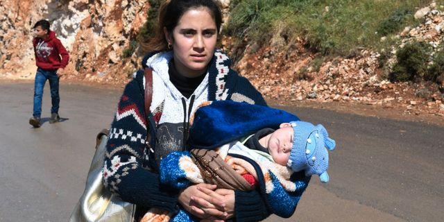 En kvinna bär på sitt barn på flykt undan Afrin.  GEORGE OURFALIAN / AFP