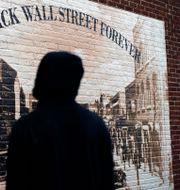 En man står framför en väggmålning som förestället Black Wall Street före rasistattacken som förstörde hela distriktet, i Greenwood i Tulsa, Oklahoma.  John Locher / TT NYHETSBYRÅN