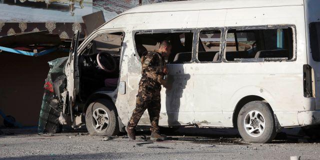 En person ur den afghanska säkerhetsstyrkorna undersöker minibussen som exploderade.  Rahmat Gul / TT NYHETSBYRÅN