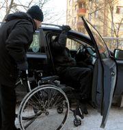 En färdtjänstchaufför hjälper en kund in i taxin. JANERIK HENRIKSSON / TT / TT NYHETSBYRÅN
