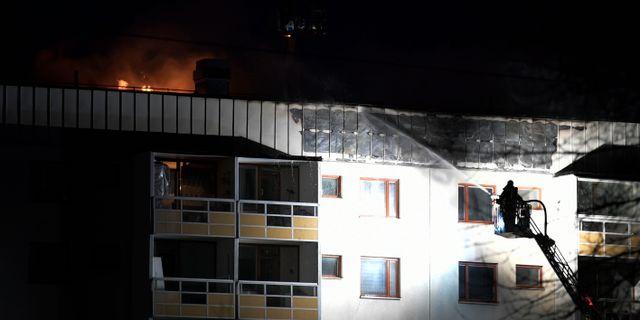 Räddningstjänsten vid taket till huset i Hagsätra som började brinna under söndagseftermiddagen. Janerik Henriksson/TT / TT NYHETSBYRÅN