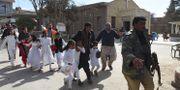 Gudsttänstbesökare evakueras efter självmordsdådet. BANARAS KHAN / AFP