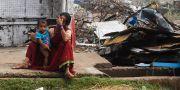 En kvinna och hennes barn sitter vid sitt förstörda hus i kuststaden Puri.  DIBYANGSHU SARKAR / AFP