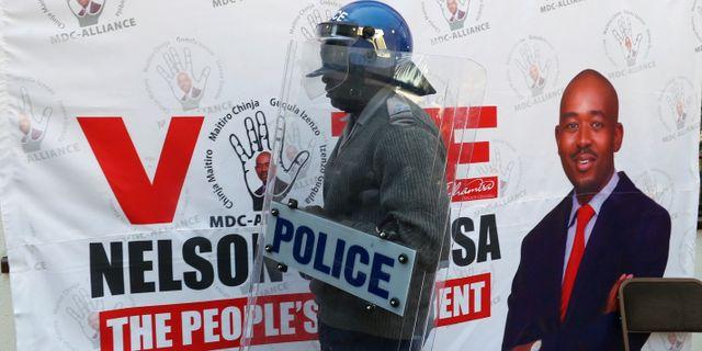 Polis framför en bild på Nelson Chamisa. MIKE HUTCHINGS / TT NYHETSBYRÅN