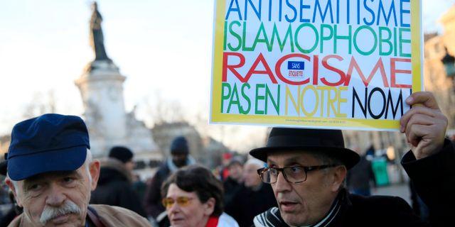 """Människor deltar i en protest mo antisemitism i Paris. Antisemitism, islamofobi, rasism – inte i våra namn"""", står det på skylten. GONZALO FUENTES / TT NYHETSBYRÅN"""