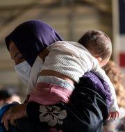 En kvinna med sitt barn på en flygplats i Italien, efter att ha flytt från Afghanistan. Giuseppe Distefano / TT NYHETSBYRÅN
