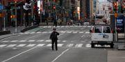 En polis på ett folktomt Times Square i New York. BRENDAN MCDERMID / TT NYHETSBYRÅN