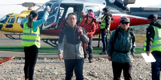 Turister på säker mark efter att ha räddats ur lavinen. KRISHNA MANI BARAL / AFP
