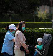 Två kvinnor promenerar med ett barn i Peking.  Andy Wong / TT NYHETSBYRÅN