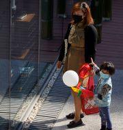 Illustrationsbild: En kvinna och ett barn i ett shoppingdistrikt i Peking, oktober 2020.  Ng Han Guan / TT NYHETSBYRÅN