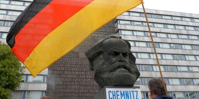 Illustrationsbild: Tyska flaggan framför en Karl Marx-byst i Chemnitz, östra Tyskland.  Jens Meyer / TT NYHETSBYRÅN
