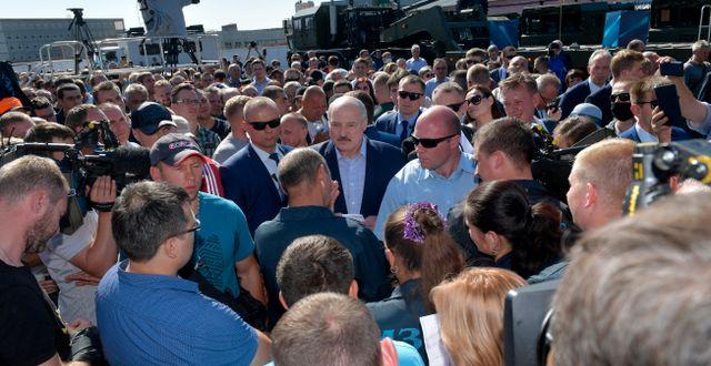 Aleksandr Lukasjenko (i mitten) omgiven av sina livvakter vid fabriken i Minsk Andrei Stasevich / TT NYHETSBYRÅN
