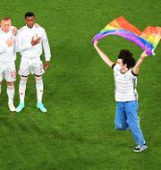 En man viftar med regnbågsflaggan framför det ungerska landslaget.  MATTHIAS HANGST / BILDBYRÅN