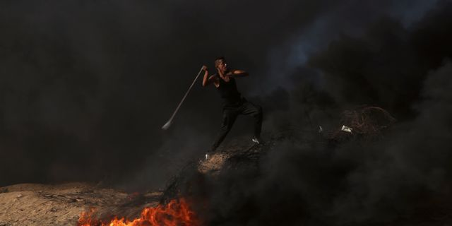 En palestinsk demonstrant kastar sten mot gränsen mot Israel. Adel Hana / TT / NTB Scanpix