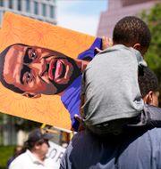 Ung pojke bär på en skylt med George Floyds porträtt i Minneapolis. Jim Mone / TT NYHETSBYRÅN