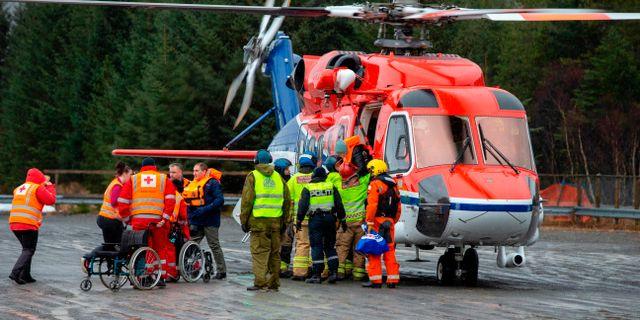 Evakuerade personer får hjälp från den helikopter som använts i räddningsinsatsen. SVEIN OVE EKORNESVAAG / NTB Scanpix