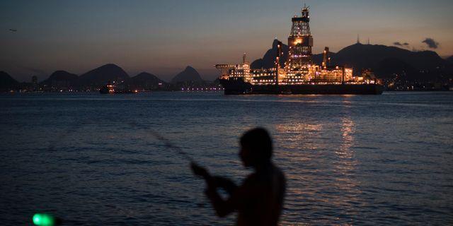 Fiskare framför en oljerigg i Guanabara Bay, Brasilien.  Leo Correa / TT NYHETSBYRÅN