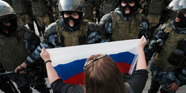 En kvinna håller en rysk flagga mot kravallpolisen. TT NYHETSBYRÅN/ NTB Scanpix