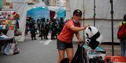 En gatuförsäljare i Hongkong packar upp sina varor framför kravallpolis på onsdagen.  Kin Cheung / TT NYHETSBYRÅN