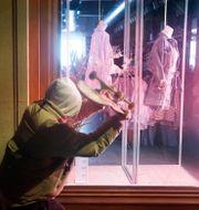 En person slår in ett butiksfönster på Barcelonas lyxshoppinggata Passeig de Gracia på lördagen.  Joan Mateu / TT NYHETSBYRÅN
