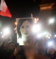 Demonstration där en person håller upp en bild på Daphne Caruana Galizia.  TT NYHETSBYRÅN
