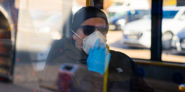 Man i munskydd på buss.  Thomas Brun / TT NYHETSBYRÅN