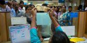 En banktjänsteman vid en bank i indiska Ghauti granskar en rupiesedel, medan människor väntar på att få växla in sina sedlar. Anupam Nath / TT / NTB Scanpix