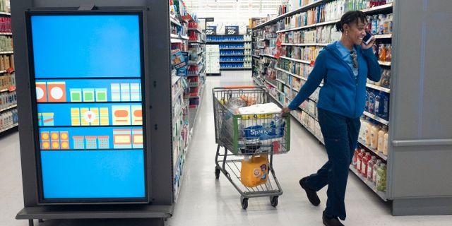 En kvinna drar en kundvagn inne på en Walmart-butik.  Mark Lennihan / TT NYHETSBYRÅN/ NTB Scanpix