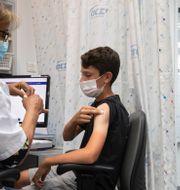 Unga israeler vaccineras med Pfizervaccinet. Sebastian Scheiner / TT NYHETSBYRÅN