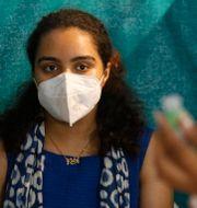 Kvinna väntar på sin första dos i Ahmedebad i Indien. Ajit Solanki / TT NYHETSBYRÅN