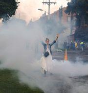 En kvinna höjer sina armar i tårgasmolnen vid sammandrabbningar mellan demonstranter och polis i Bogota i helgen Fernando Vergara / TT NYHETSBYRÅN