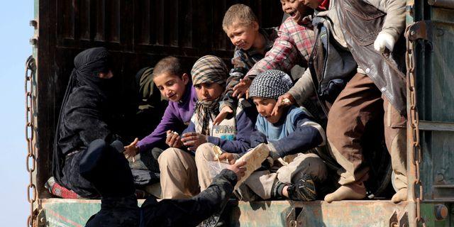 En soldat från SDF ger barn bröd i närheten av Baghuz i Syrien.  RODI SAID / TT NYHETSBYRÅN