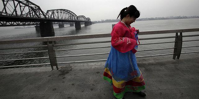Turist med traditionella koreanska kläder vid bron mellan Kina och Nordkorea i gränsstaden Dandong. Arkivbild. TT