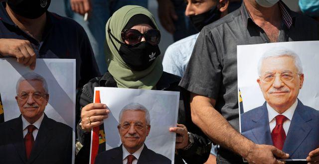 Palestinier håller bilder på Mahmoud Abbas i händerna.  Majdi Mohammed / TT NYHETSBYRÅN