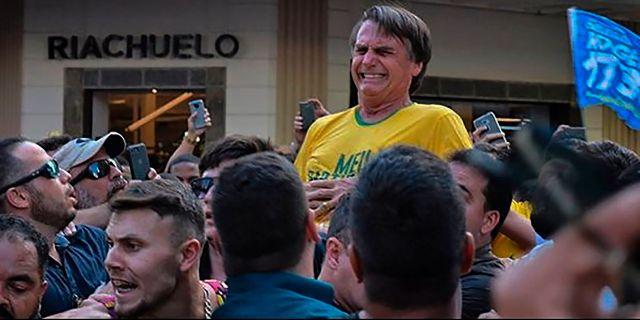 Bolsonaro tar sig mot magen efter knivhugget. RAYSA LEITE / AFP