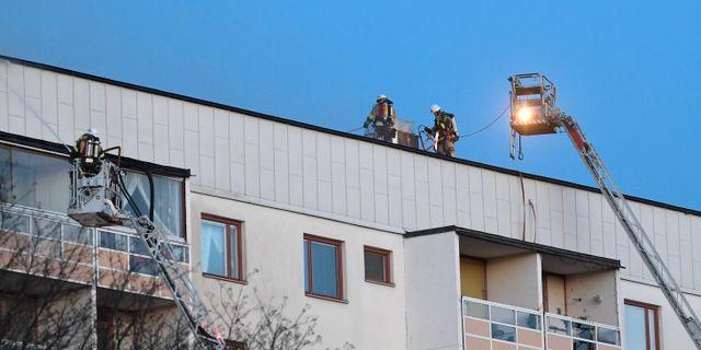 Räddningstjänsten på taket till huset i Hagsätra som började brinna under söndagseftermiddagen. Janerik Henriksson/TT / TT NYHETSBYRÅN