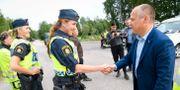 Johansson hälsar på polis på plats i Broddbo på onsdagen. Fredrik Sandberg/TT / TT NYHETSBYRÅN