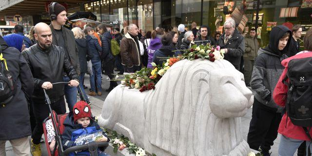 På årsdagen av terrordådet på Drottninggatan i Stockholm lägger människor blommor på betonglejonen vid det hörn av Åhléns City som Rakhmat Akilovs kapade lastbil kraschade in i.  Claudio Bresciani/TT / TT NYHETSBYRÅN