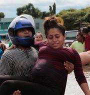 En gravid kvinna bärs ut från ett översvämmat område i Honduras efter att stormen Eta dragit in över landet.  Delmer Martinez / TT NYHETSBYRÅN