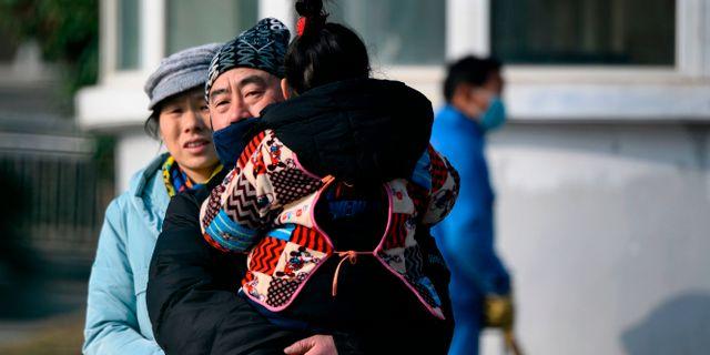 En familj lämnar det sjukhus i Wuhan där det första dödsfallet nyligen bekräftades. NOEL CELIS / AFP