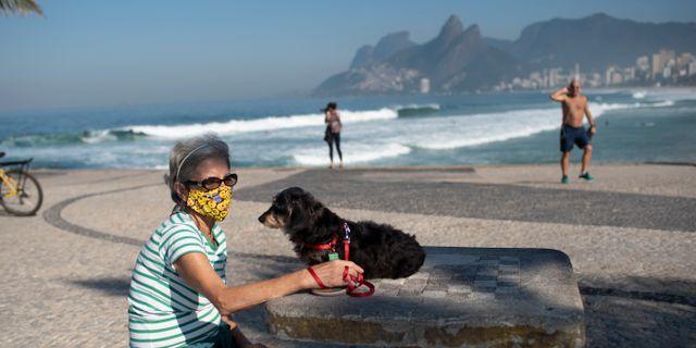 Lokalbon Lucia med sin hund Jujuba gick till stranden Arpoador i Rio de Janeiro när staden öppnade idag. Silvia Izquierdo / TT NYHETSBYRÅN
