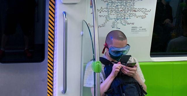 Kinesisk pendlare i huvudstaden iförd skyddsglasögon och mask.  Andy Wong / TT NYHETSBYRÅN
