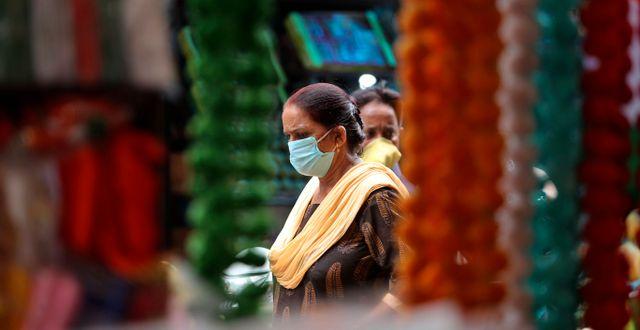 Kvinna i munskydd på marknad i Jammu, Indien.  Channi Anand / TT NYHETSBYRÅN