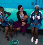 Kvinnor väntar på testresultat efter en virustestning i Johannesburg. Denis Farrell / TT NYHETSBYRÅN