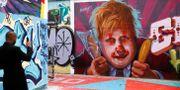 En man fotograferar en graffitivägg föreställande Boris Johnson.  HENRY NICHOLLS / TT NYHETSBYRÅN