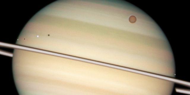 Saturnus med sina månar. Titan är den stora orangea till höger.  NASA / SCANPIX