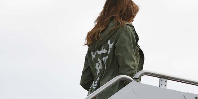 Melania Trump sågs i jackan när hon gick ombord planet till gränsen.  MANDEL NGAN / AFP
