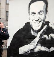 Polis framför en grafittimålning föreställande Navalnyj. Ivan Petrov / TT NYHETSBYRÅN