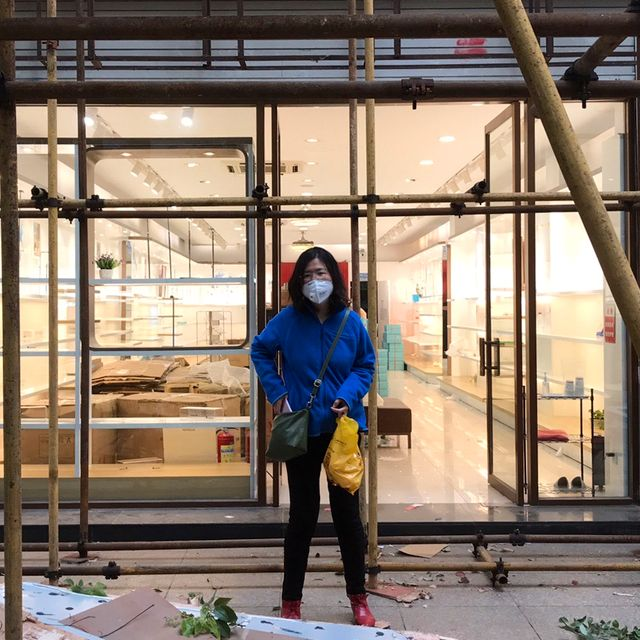 In this photo taken April 11, 2020 and released by Melanie Wang, Zhang Zhan stand near scaffoldings outside a shop during a visit to Wuhan in central China's Hubei province. TT NYHETSBYRÅN