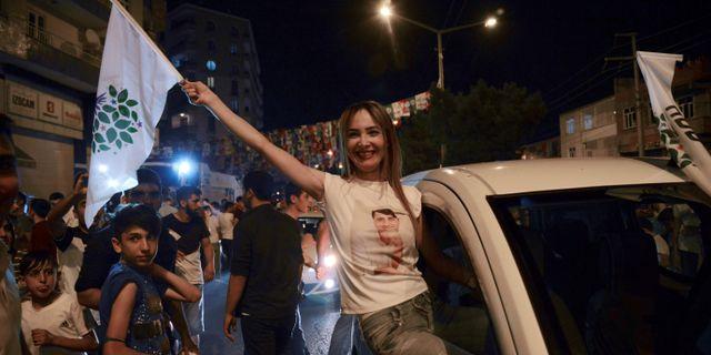 Människor firar det prokurdiska partiet HDP:s framgångar i parlamentsvalet i staden Diyarbakir.  ILYAS AKENGIN / AFP
